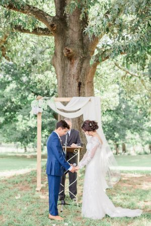 Beautiful outdoor ceremony again arbor with hydrangeas and draped fabric. Davids Bridal wedding dress. Ceremony at a tree. Hays McDonald Farm.