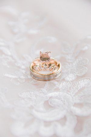 Romantic rose gold alternative wedding rings on a lace wedding dress.