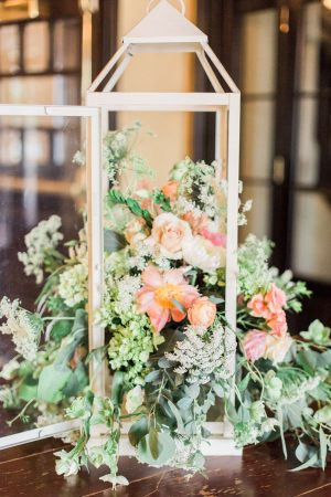 Bird cage lantern floral centerpiece with roses, peonies, and greenery at The Historic Rice Mill in Charleston.