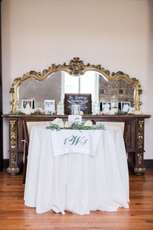 Sweetheart table with antique rentals and monogram decor at The Historic Rice Mill in Charleston.