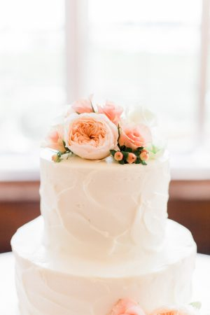 Floral wedding cake topper against antique windows at The Historic Rice Mill in Charleston.
