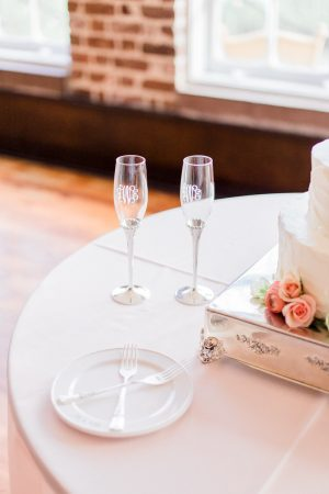 Monogrammed champagne glasses flutes on wedding cake table at The Historic Rice Mill in Charleston.