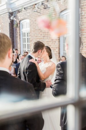 Wedding first kiss through window at The Historic Rice Mill in Charleston.