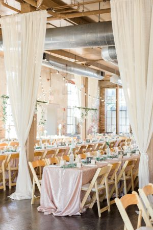Industrial wedding reception with lots of window light and hanging candles at The Mill at Yellow River.