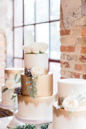 Dessert table and wedding cake with gold accents and floral details at The Mill at Yellow River.