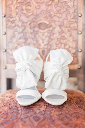 Wedding details bridal shoes photo against antique leather chair.