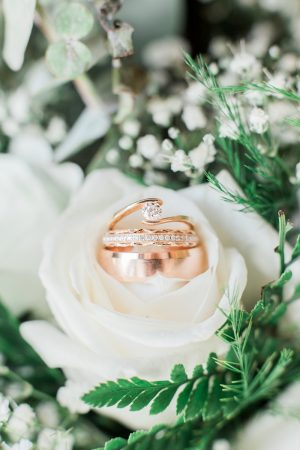 Rose gold ring shot against white wedding bouquet with babies breath, roses, and greenery.