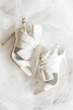 White bridal shoes on white veil wedding details.