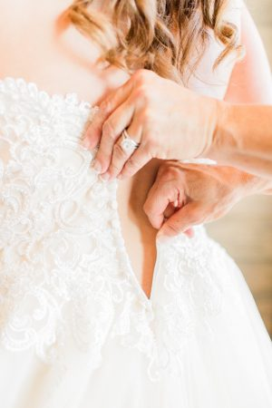 Getting ready photo. Mother of the bride buttoning up wedding dress.