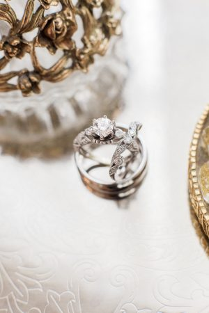 Wedding rings on silver tray with antique perfume bottle.