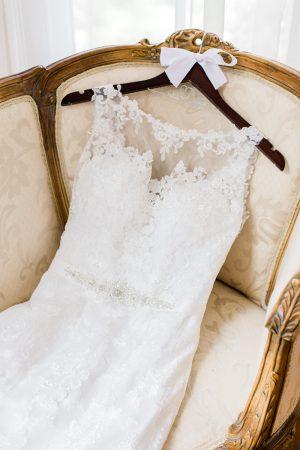 Wedding dress on custom hanger. Wedding details in antique historic wedding venue.