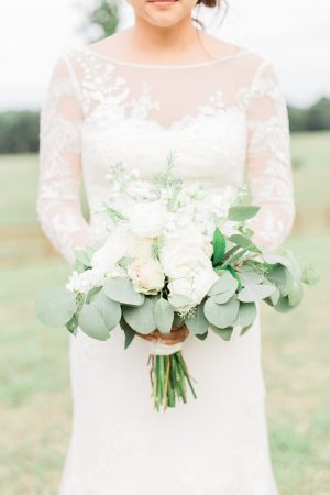 White wedding bouquet against wedding dress from Davids Bridal.