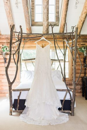 Beaded lace wedding dress hanging from unique wood canopy bed at a cabin.