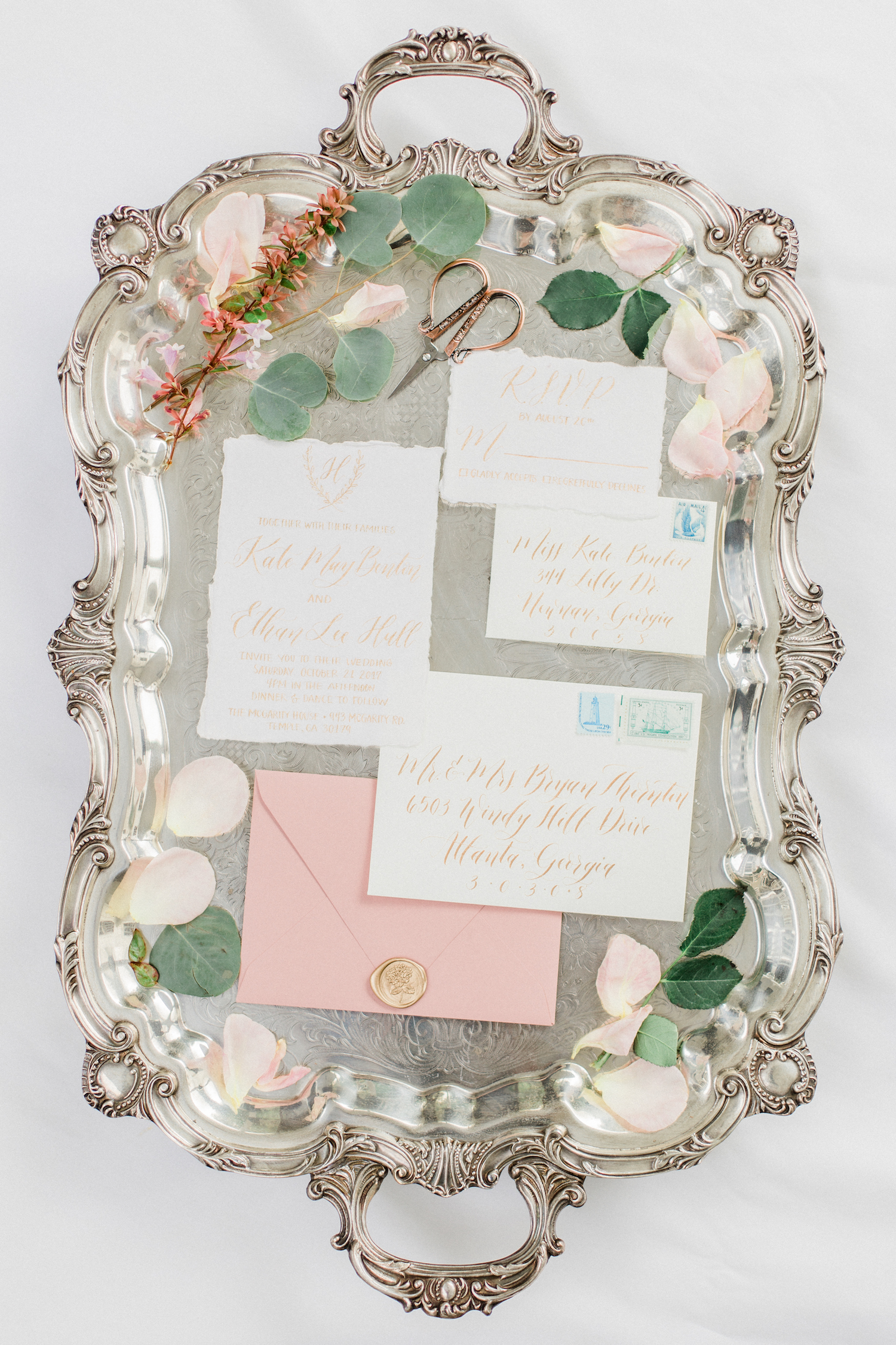 Styling invitations suite as a flat lay on an antique silver tray.