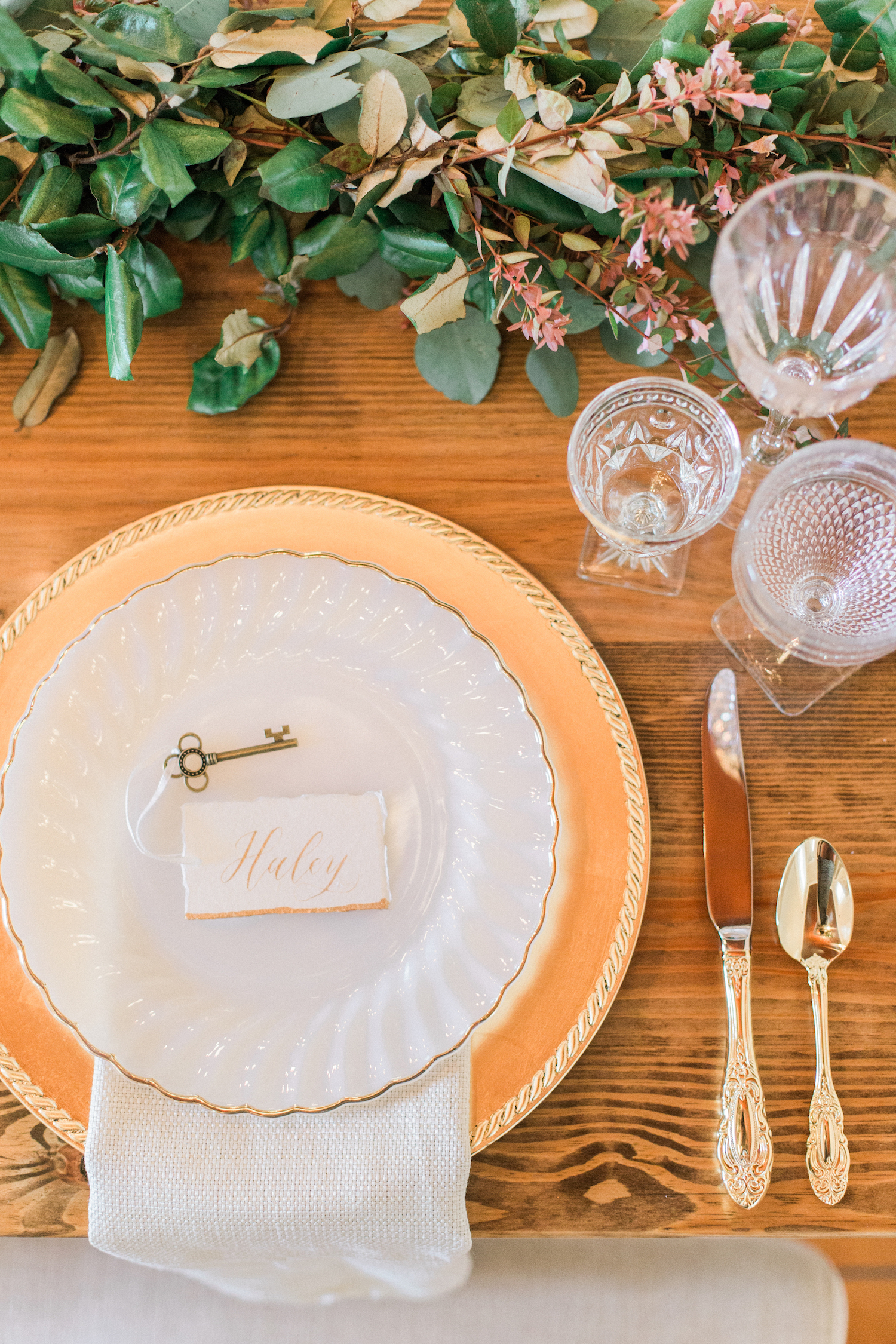 Key place cards and gold plates and silverware for wedding table setting.