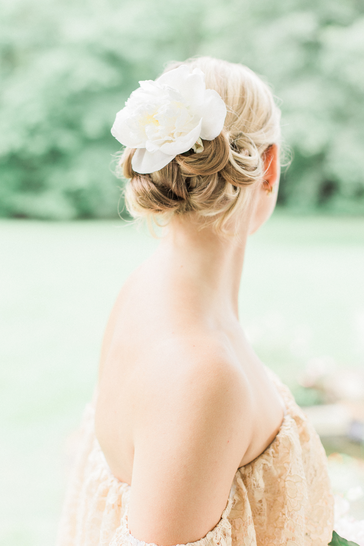 Wedding hairstyle and undo with big floral accent and accessories. Flowers in hair for wedding day.