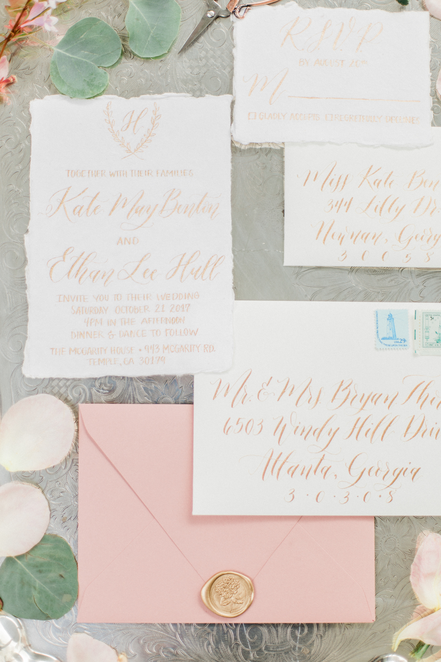 Wedding invitation suite with gold lettering, pink blush envelopes, and gold envelope stamp.