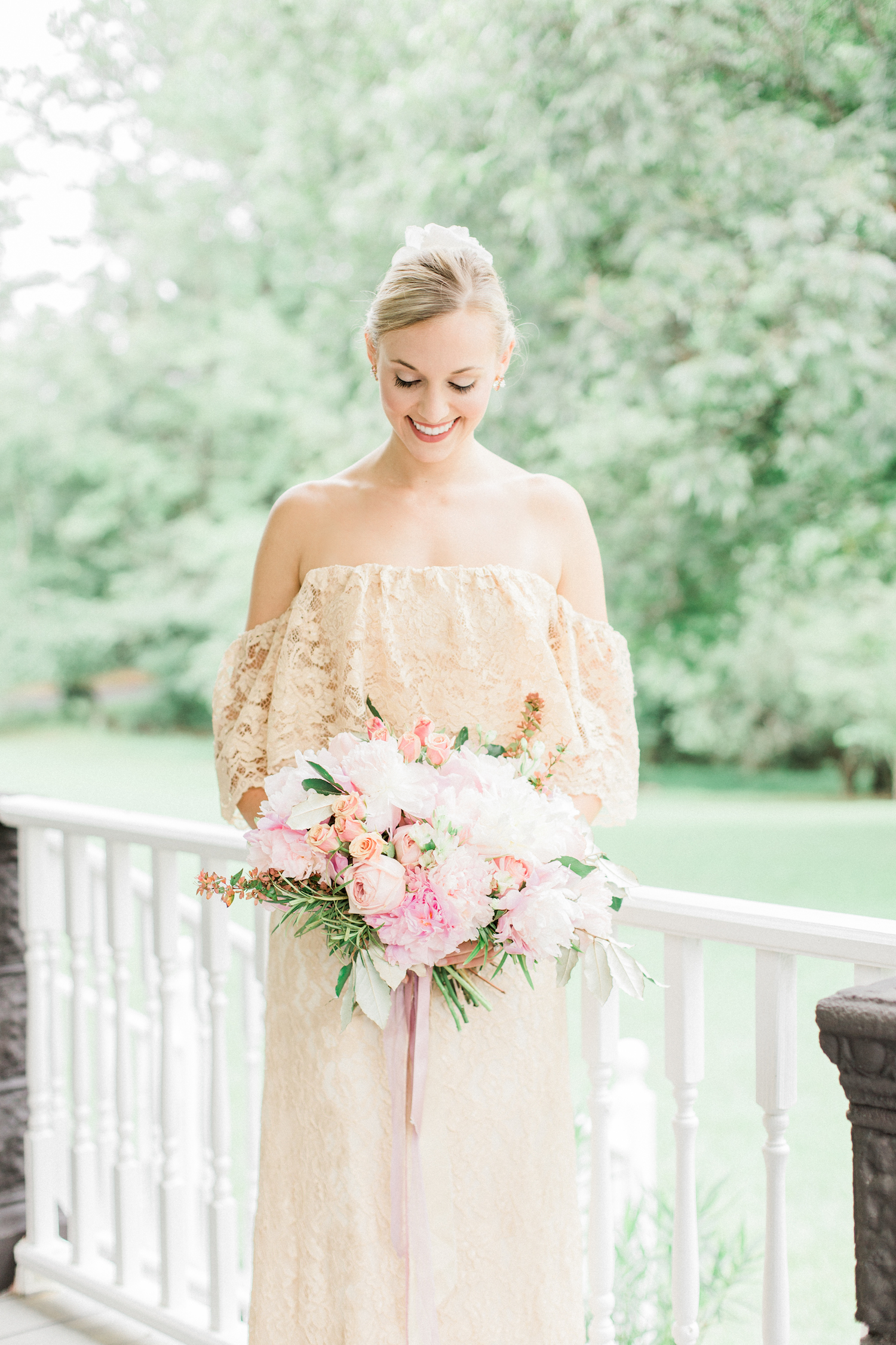 Gold off shoulder lace bohemian wedding dress with pink wedding bouquet.