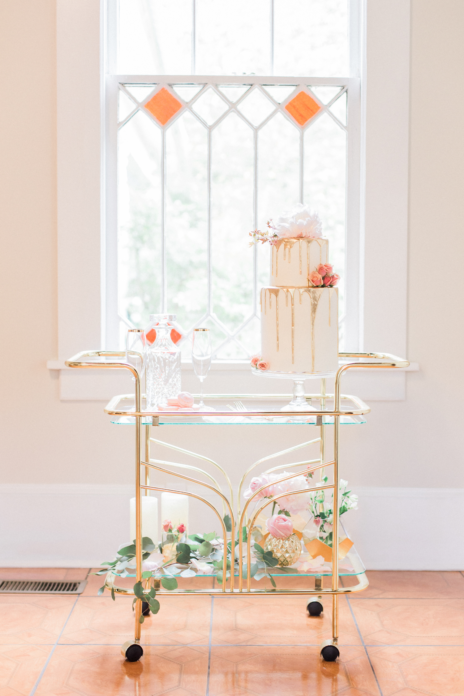 Gold dripped wedding cake with floral accents on a gold antique bar cart.