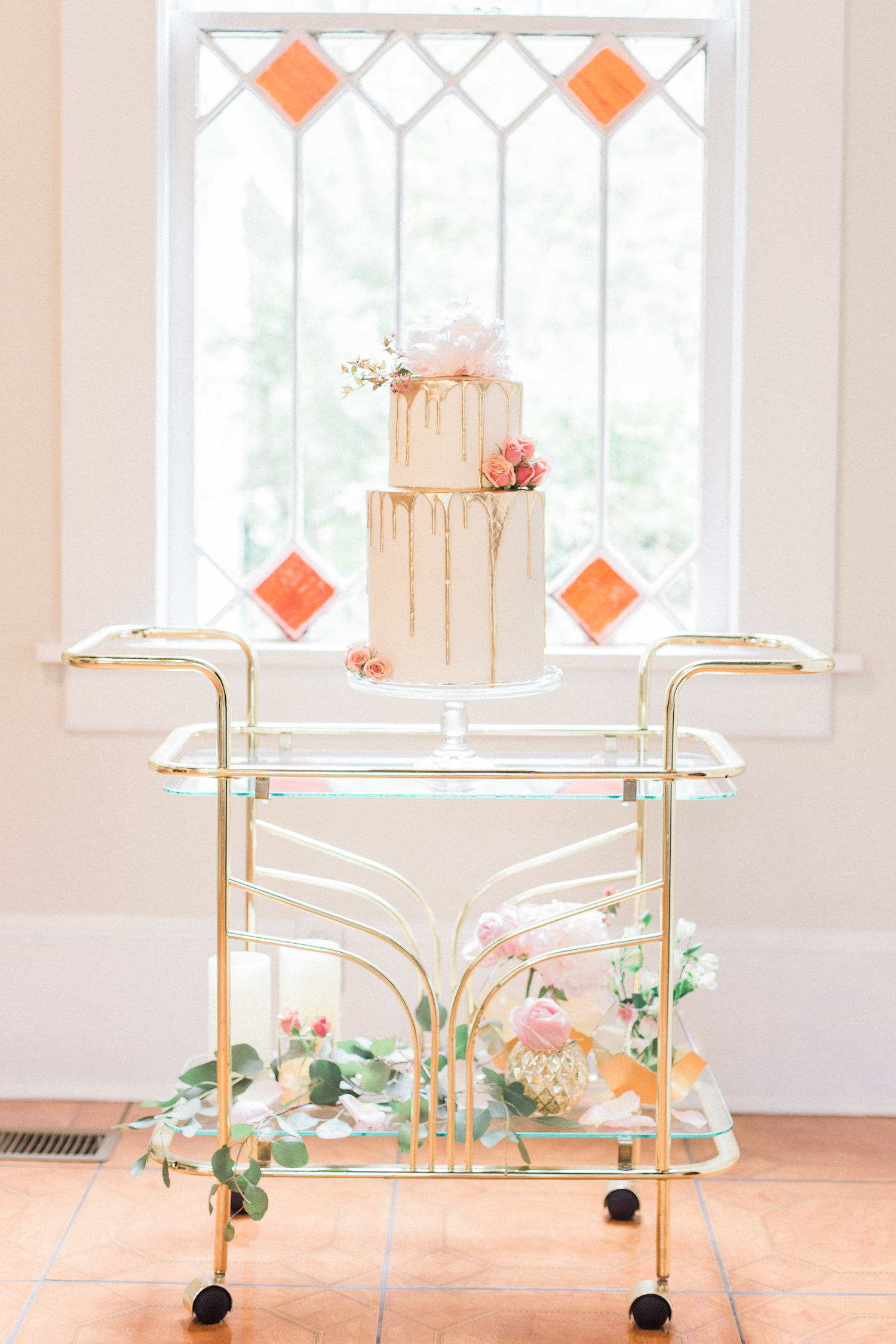 Two tier gold dripped wedding cake with roses and peonies on an antique gold bar cart.