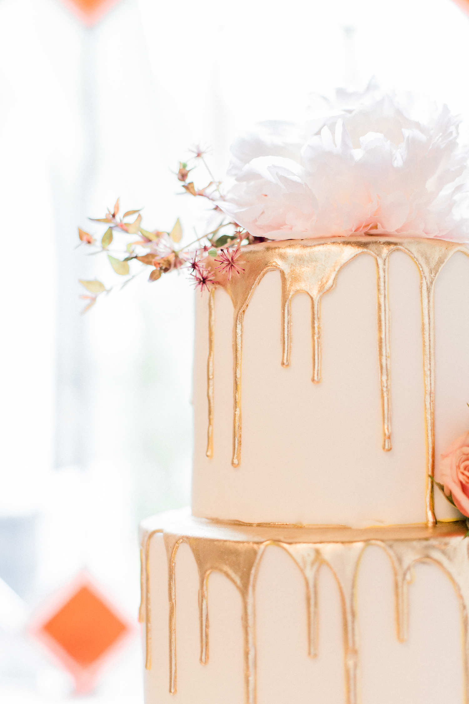 Gold dripped wedding cake with peonies.
