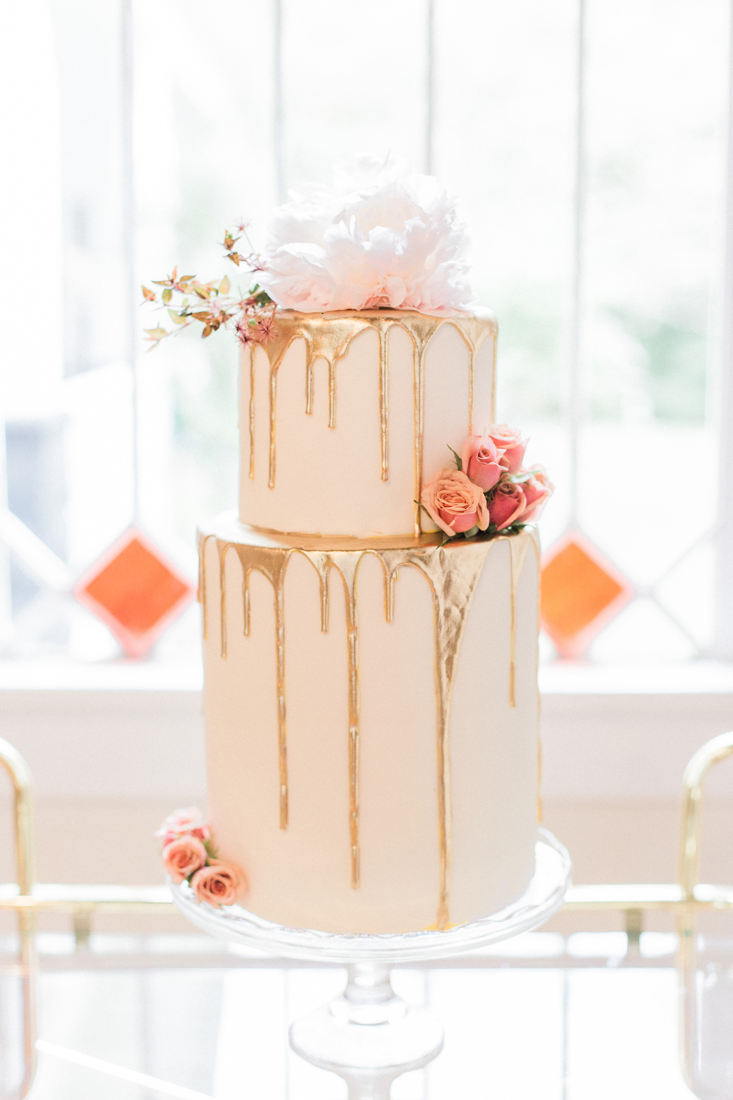Gold dripped wedding cake with roses and peonies on a antique gold bar cart.