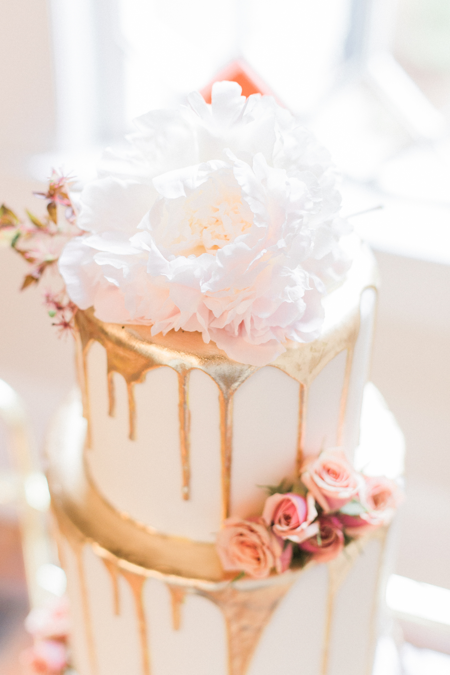 Peony cake topped on a gold dripped two tier wedding cake with roses.