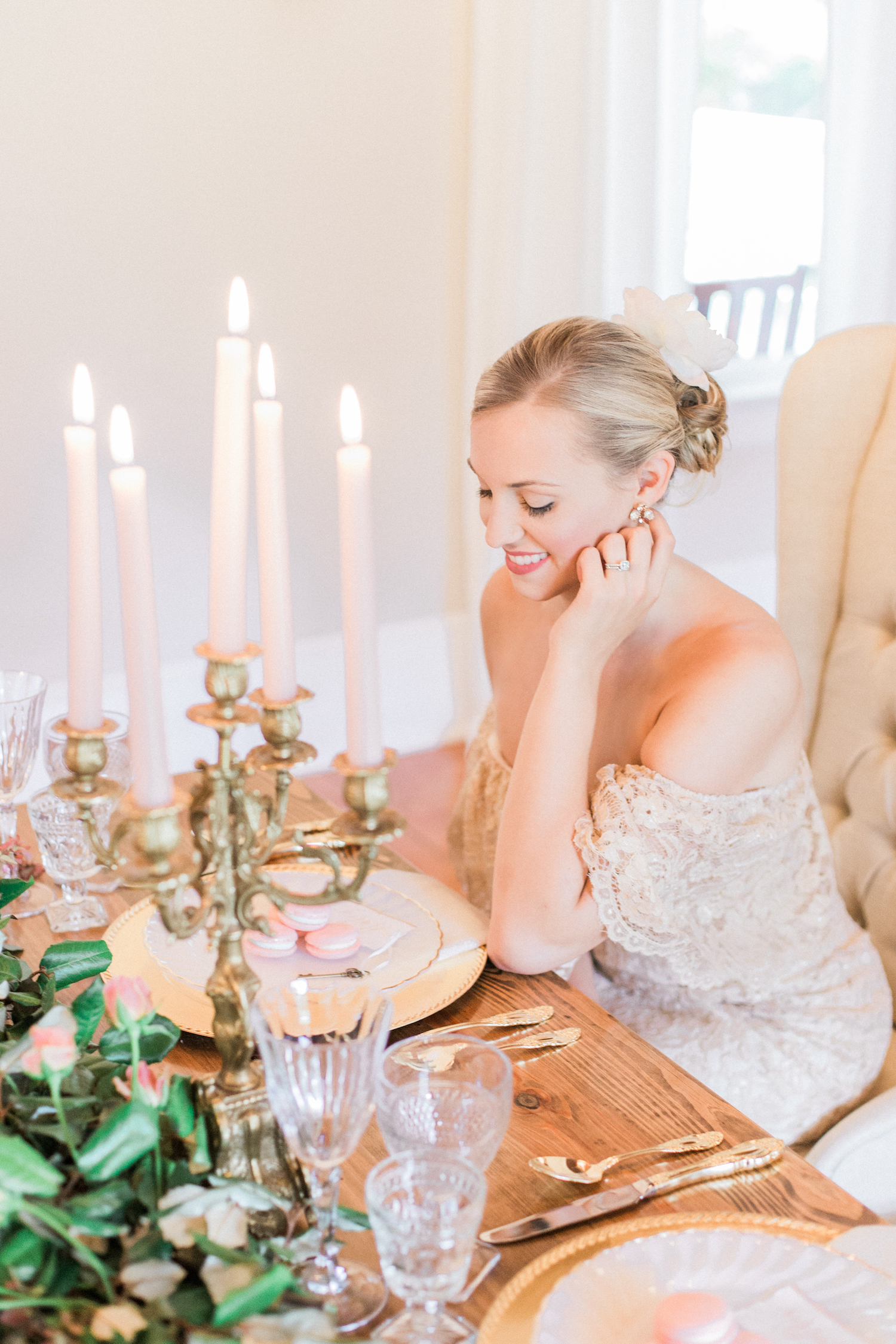 Bride sitting at sweetheart table with gold lace off shoulder wedding dress and bridal undo hair style.