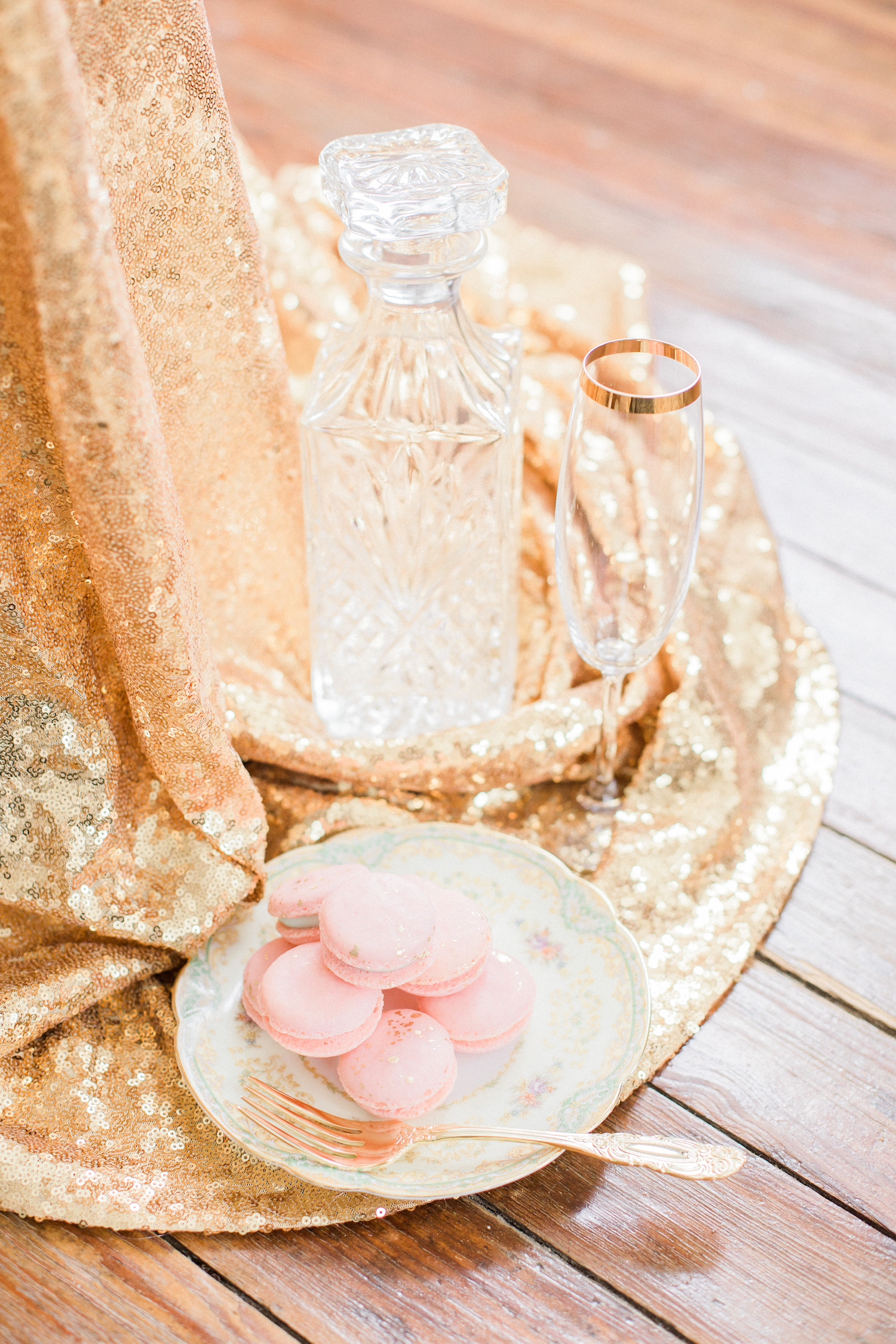 Sparkly gold getting ready room with champagne glasses and pink macaroons.