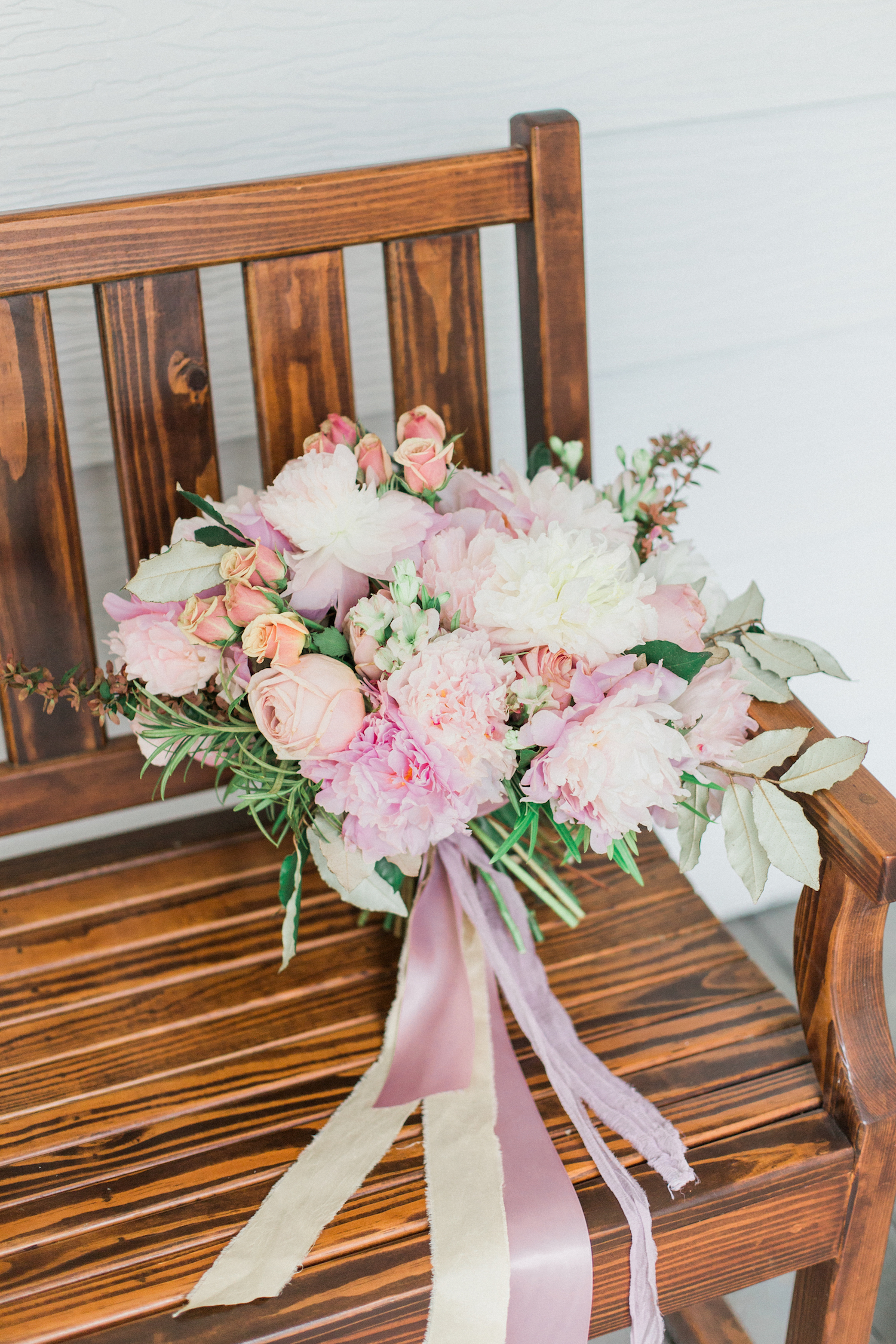 Pink mauve and blush wedding bouquet with peonies roses and greenery with silk ribbon.