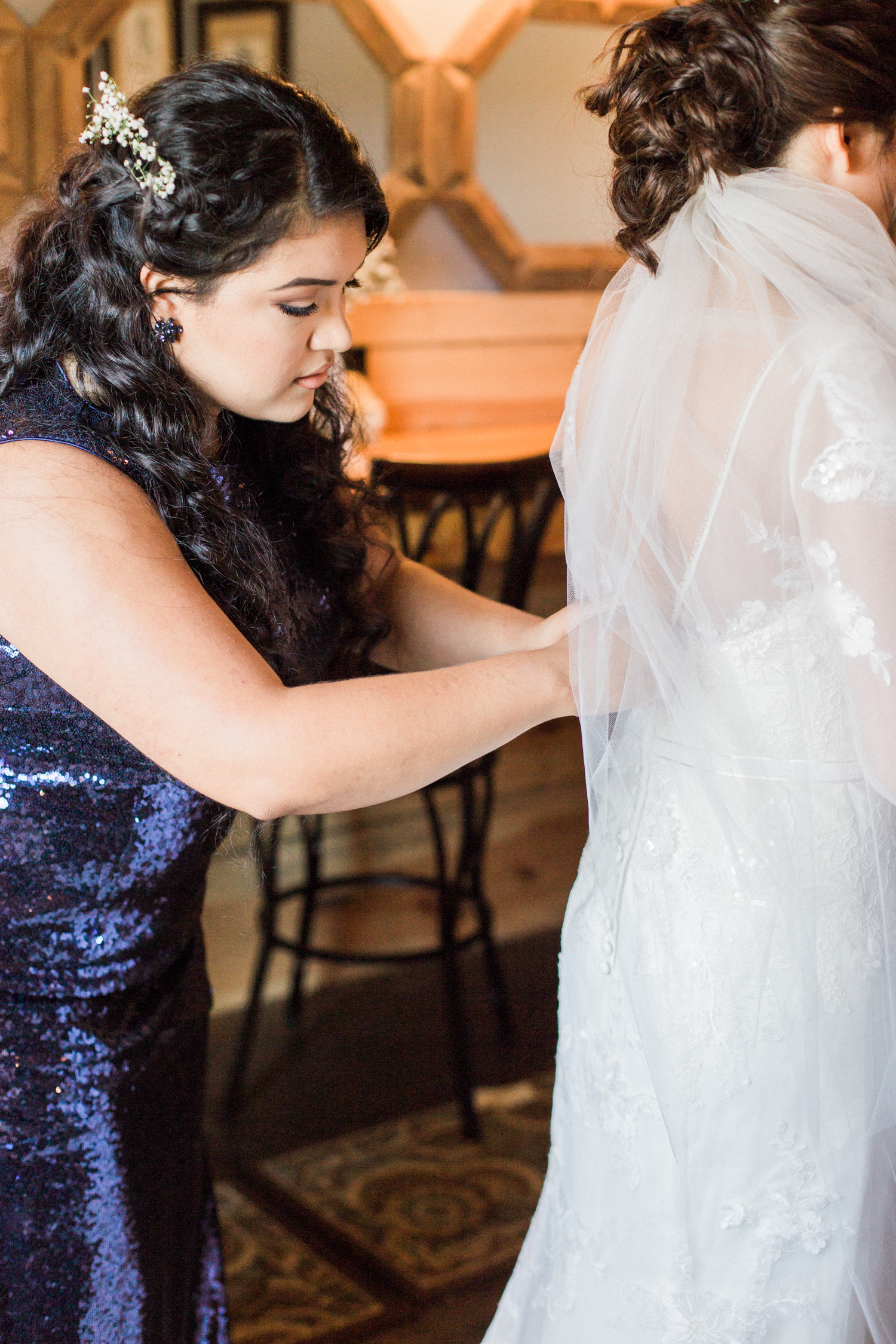 Getting ready wedding photo- bride getting buttoned into her wedding dress by her maid of honor. Summer, outdoor, barn wedding in north Georgia at Hays McDonald Farm in Jefferson, Georgia. Photo by Kesia Marie Photography - Fine Art Wedding Photographer.