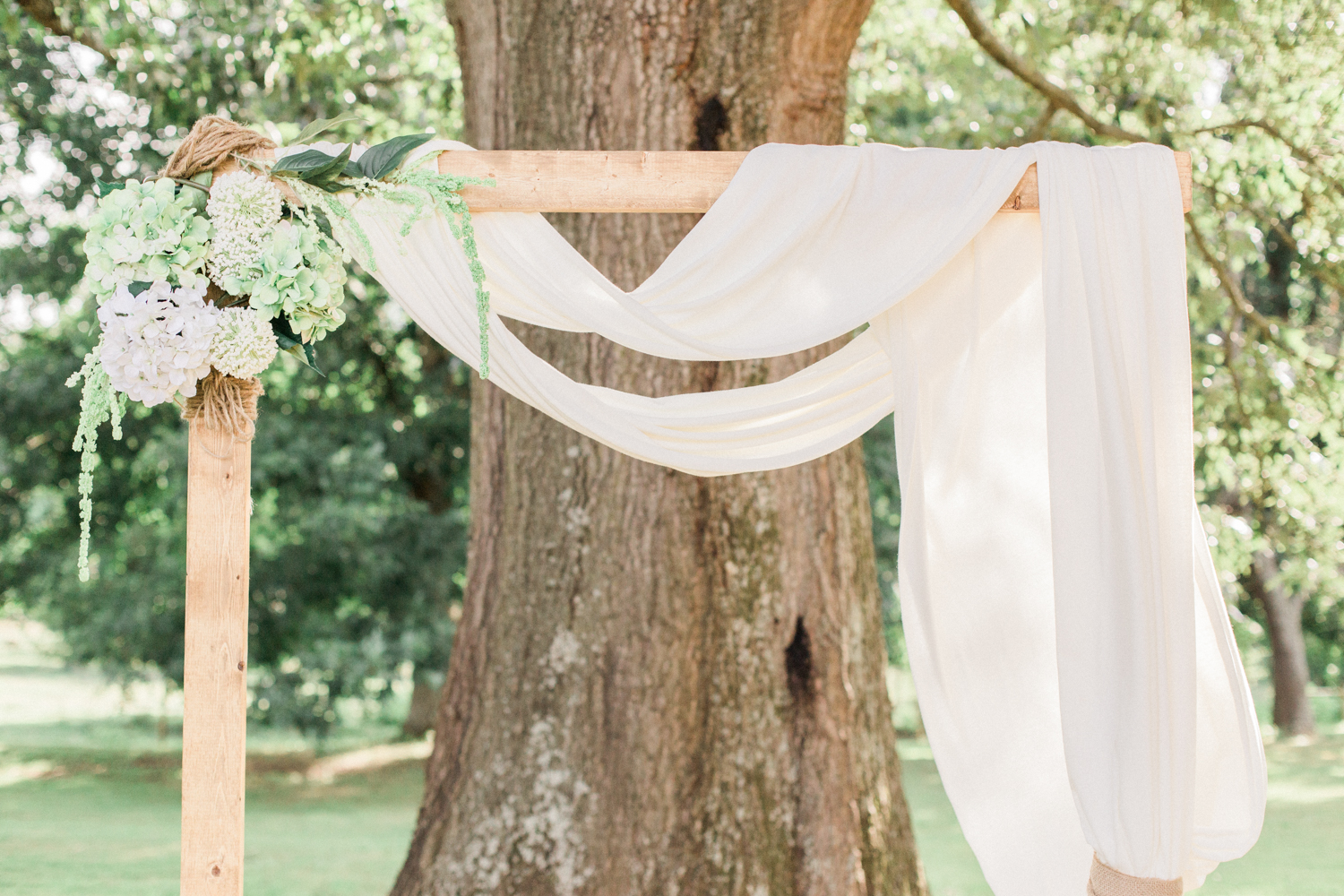Wedding ceremony arbor with hydrangeas and draped fabric. Summer, outdoor, barn wedding in north Georgia at Hays McDonald Farm in Jefferson, Georgia. Photo by Kesia Marie Photography- Fine Art Wedding Photographer.