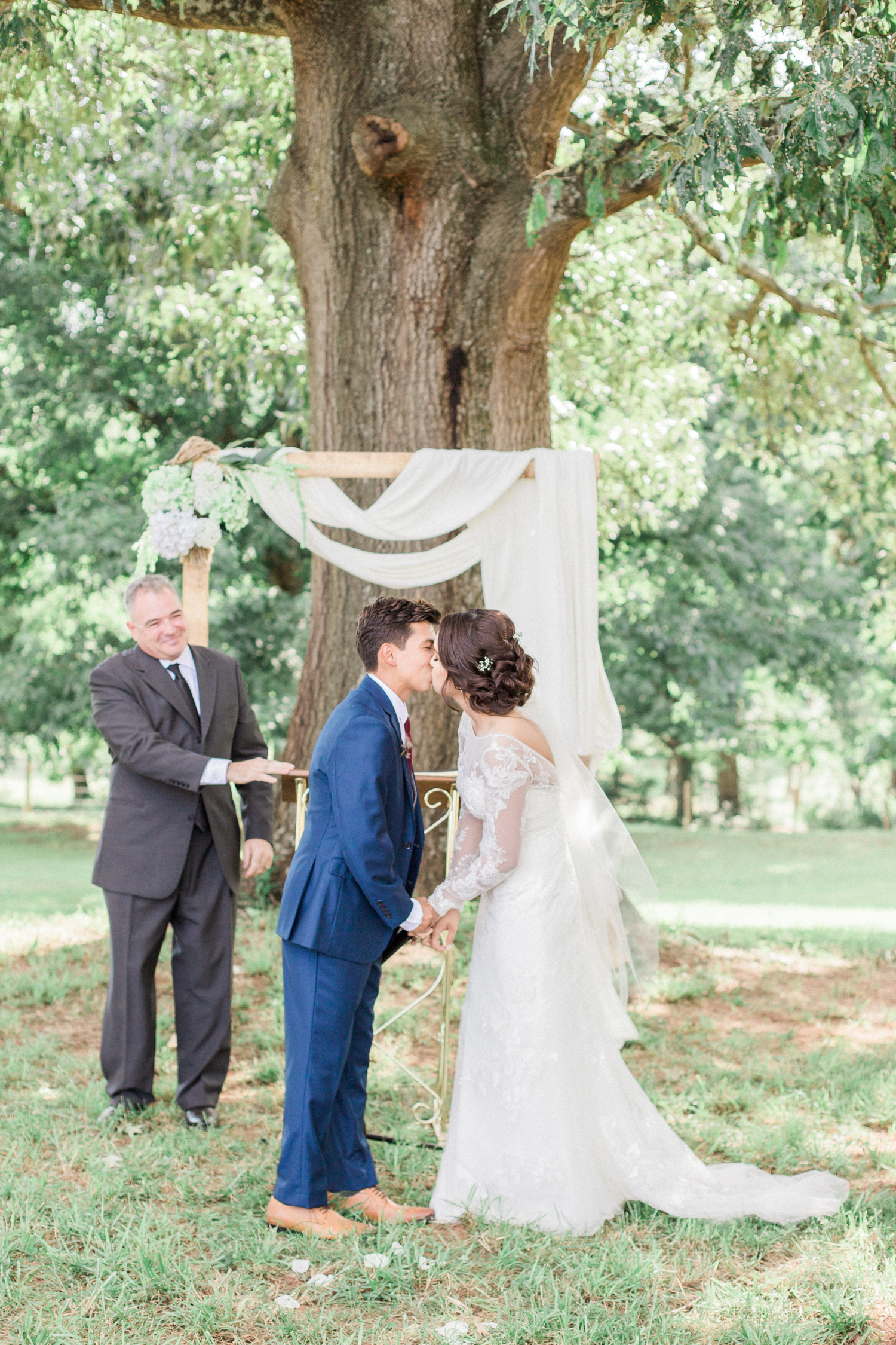 First kiss as husband and wife during an outdoor ceremony infant of a wooden arbor decorated with hydrangeas and draped fabric. Summer, outdoor, barn wedding in north Georgia at Hays McDonald Farm in Jefferson, Georgia. Photo by Kesia Marie Photography- Fine Art Wedding Photographer.