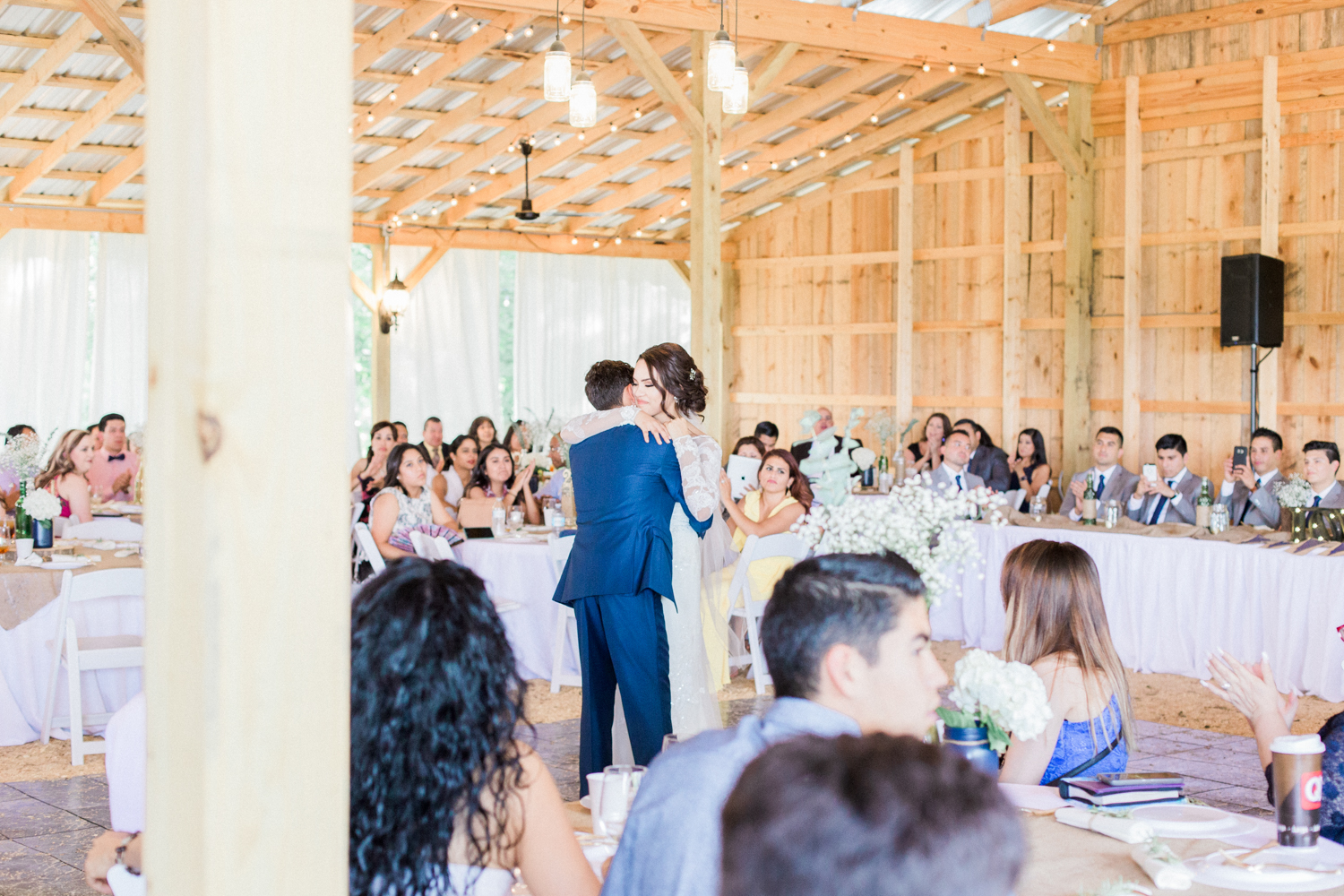 First dance as husband and wife under hanging mason jar lights in a barn with a tin roof. Summer, outdoor, barn wedding in north Georgia at Hays McDonald Farm in Jefferson, Georgia. Photo by Kesia Marie Photography- Fine Art Wedding Photographer.