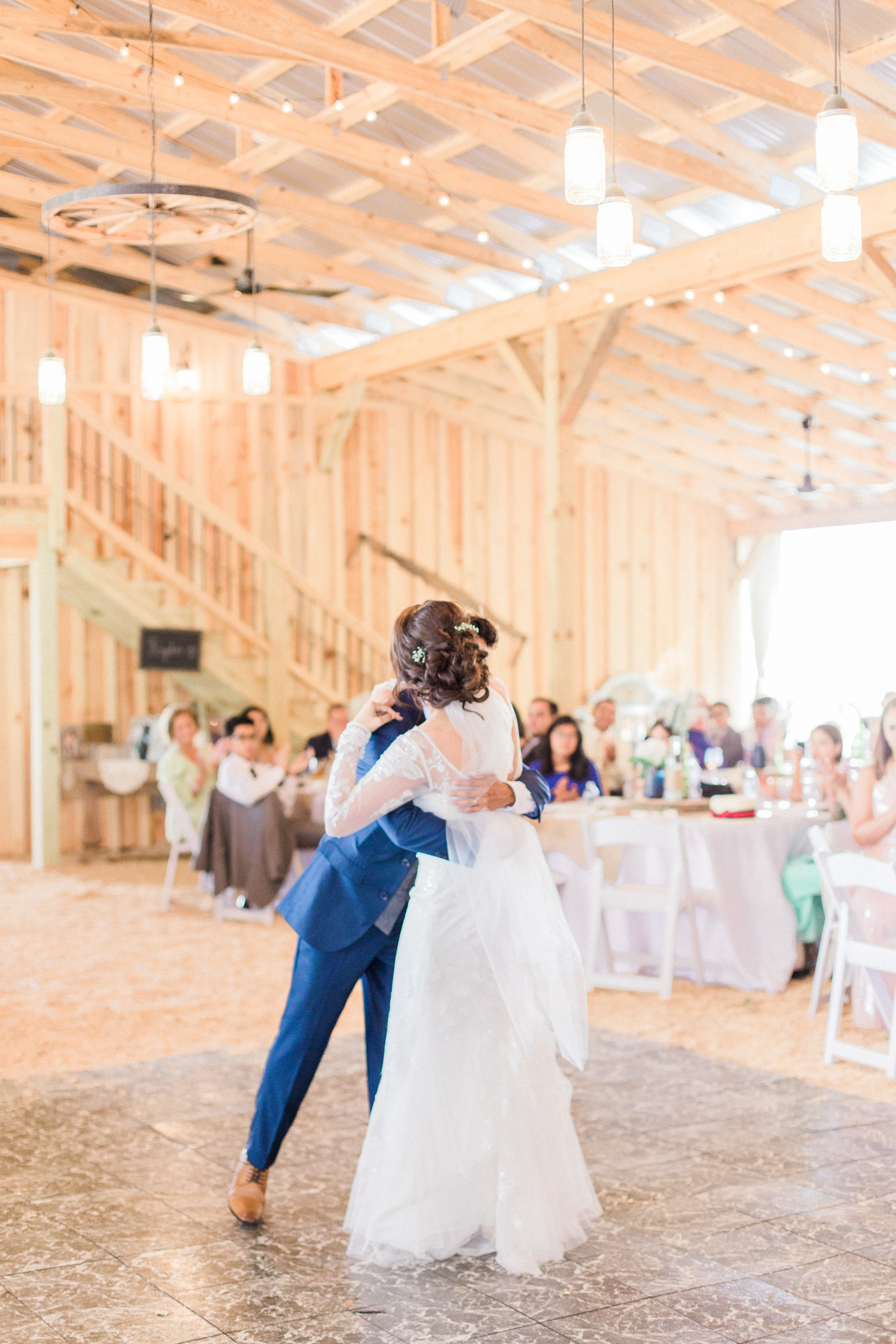 First dance as husband and wife under hanging mason jar light in a rustic barn with a tin roof. Summer, outdoor, barn wedding in north Georgia at Hays McDonald Farm in Jefferson, Georgia. Photo by Kesia Marie Photography - Fine Art Wedding Photographer.