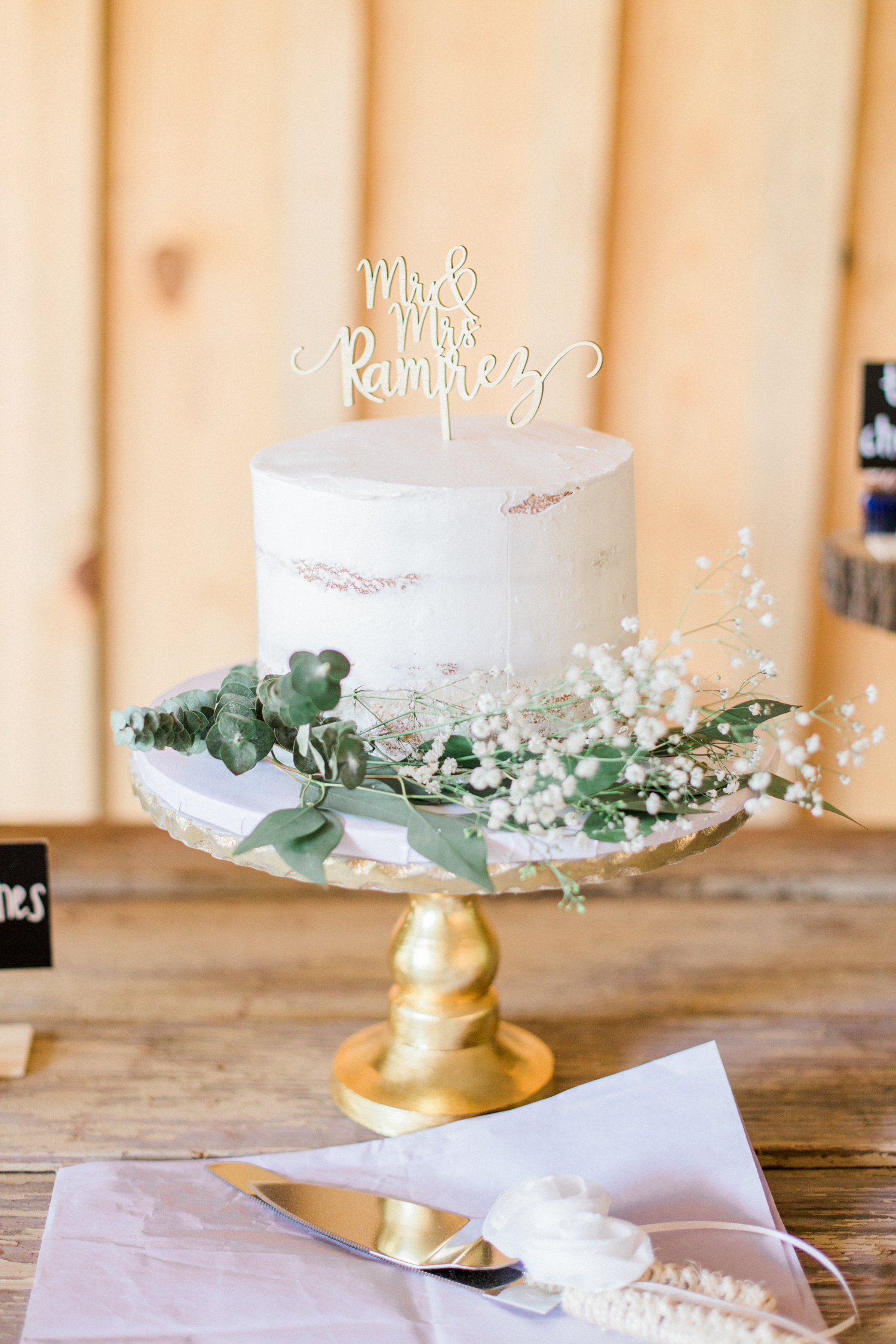 Mr and Mrs cake topper on a wedding cake decoded with baby's breath and eucalyptus. Summer, outdoor, barn wedding in north Georgia at Hays McDonald Farm in Jefferson, Georgia. Photo by Kesia Marie Photography - Fine Art Wedding Photographer.