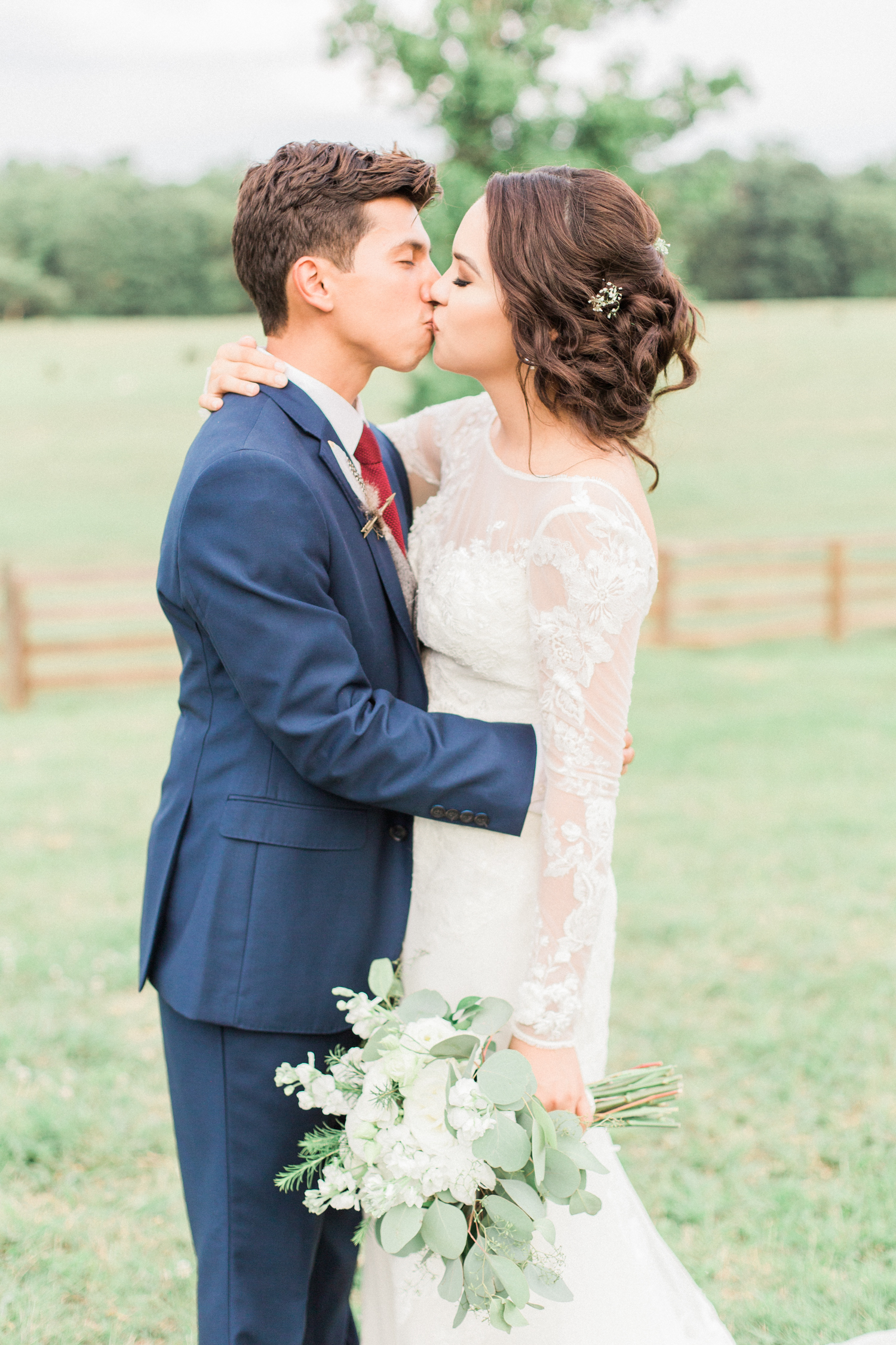 Bride and groom sharing a kiss- bride is in a long sleeved lace David's Bridal gown. Summer, outdoor, barn wedding in north Georgia at Hays McDonald Farm in Jefferson, Georgia. Photo by Kesia Marie Photography - Fine Art Wedding Photographer.