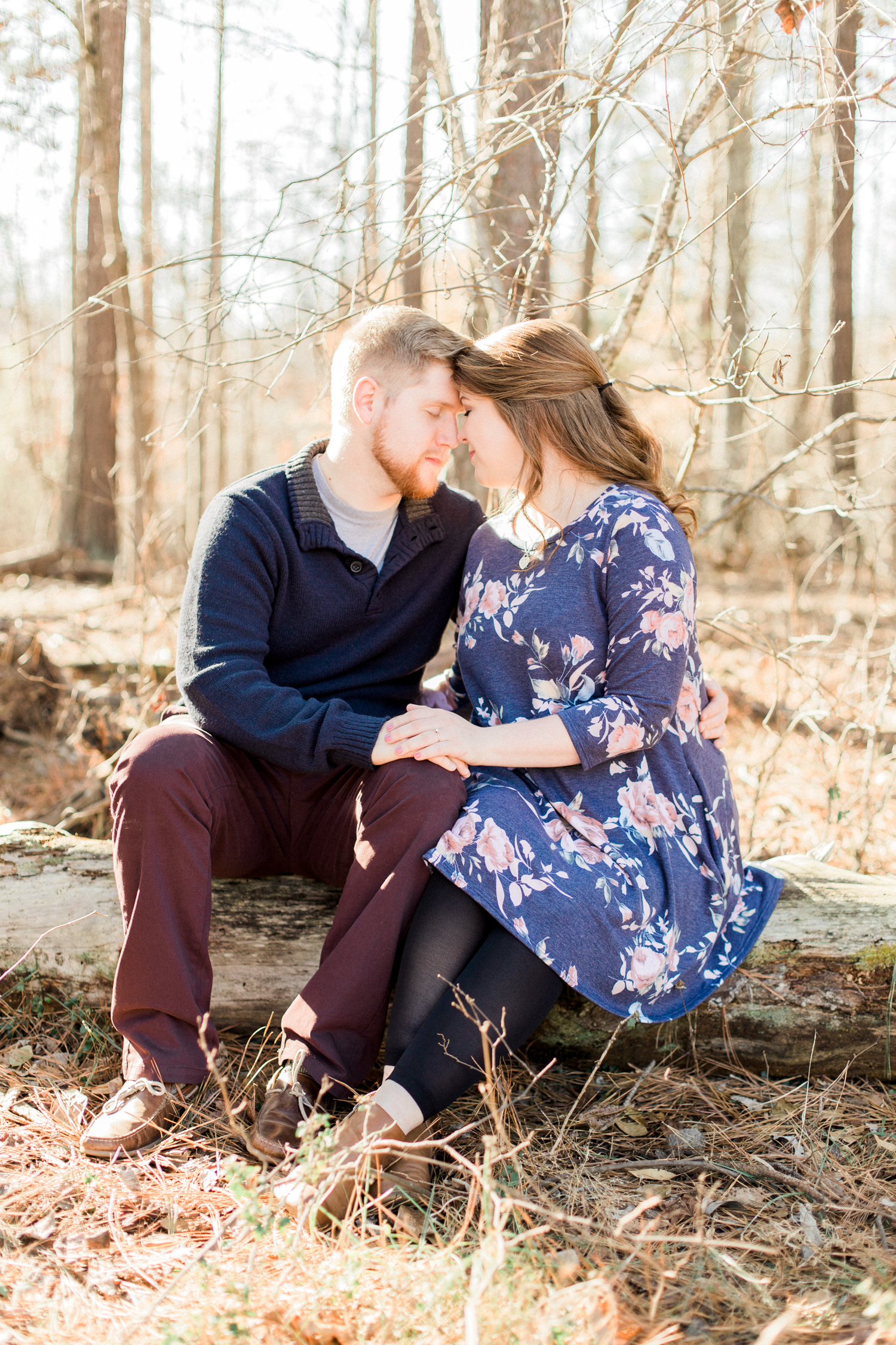 Beautiful natural-light filled winter engagement session in the woods in Marietta, Georgia. Navy and burgundy engagement session outfit style. Atlanta Fine Art Engagement photographer.
