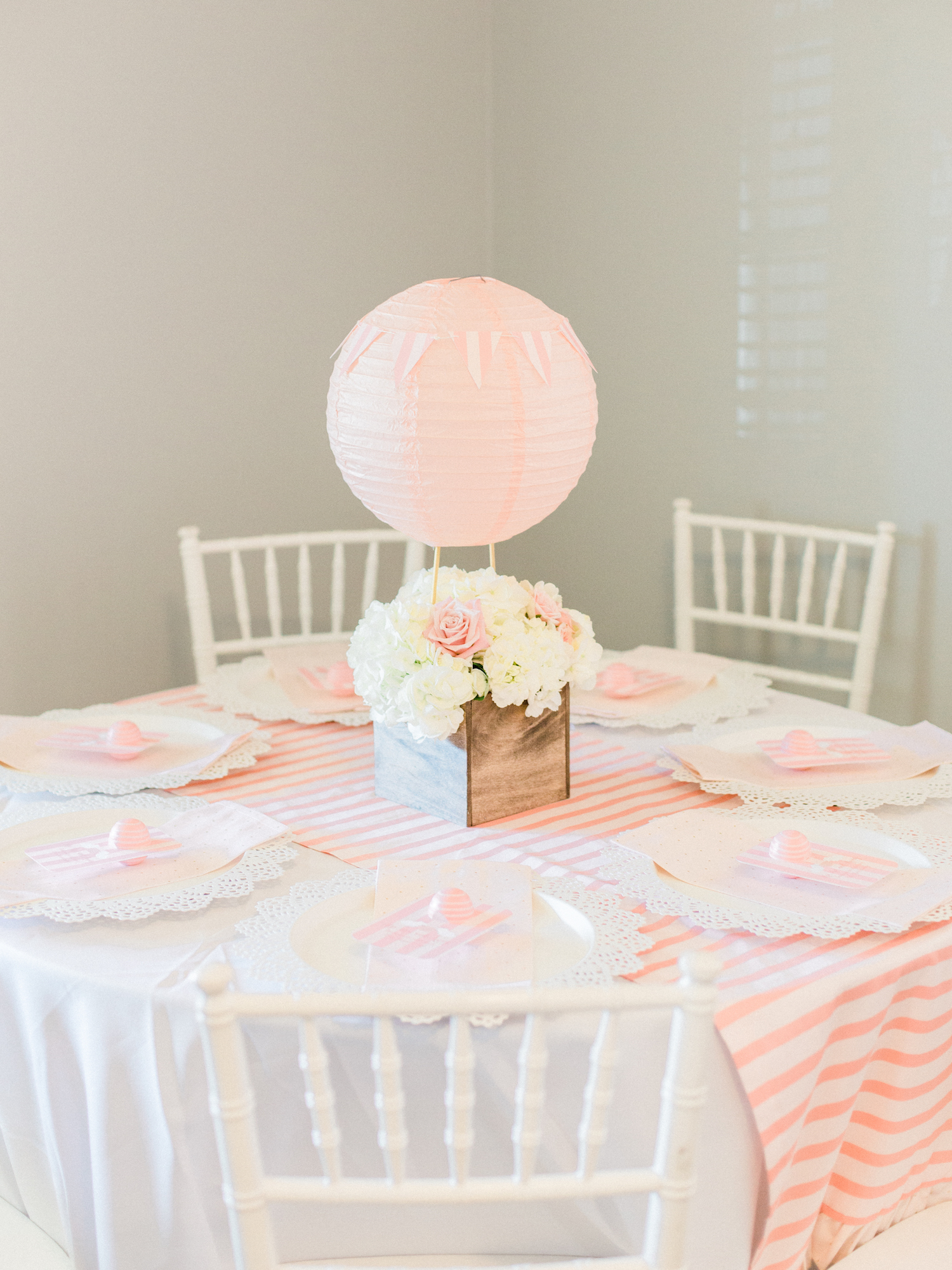 Hot air balloon floral centerpiece. Pink and white baby shower decor. White chiavari chairs.