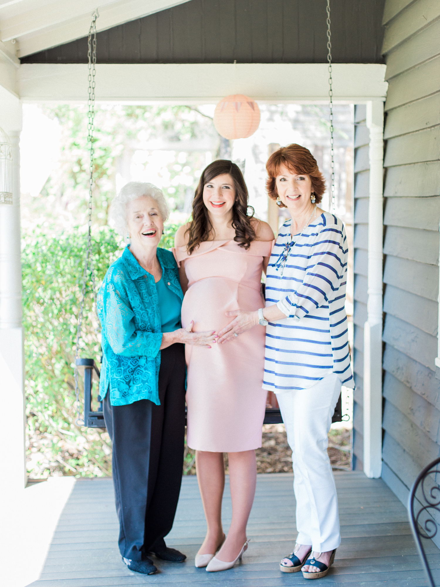 Three generations of mothers at a baby shower. Pink maternity dress.