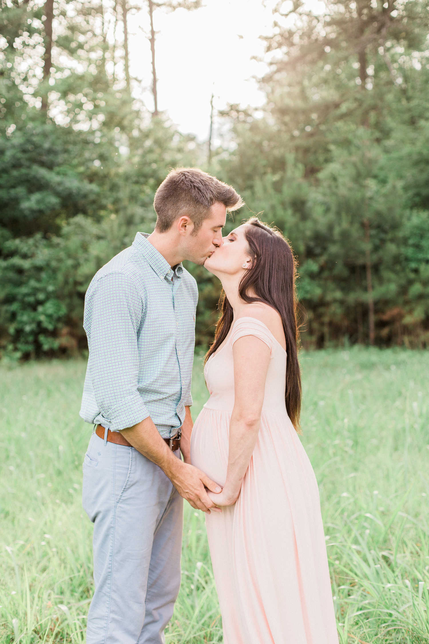 Kissing spring time maternity session photo. Blush pink maternity dress.