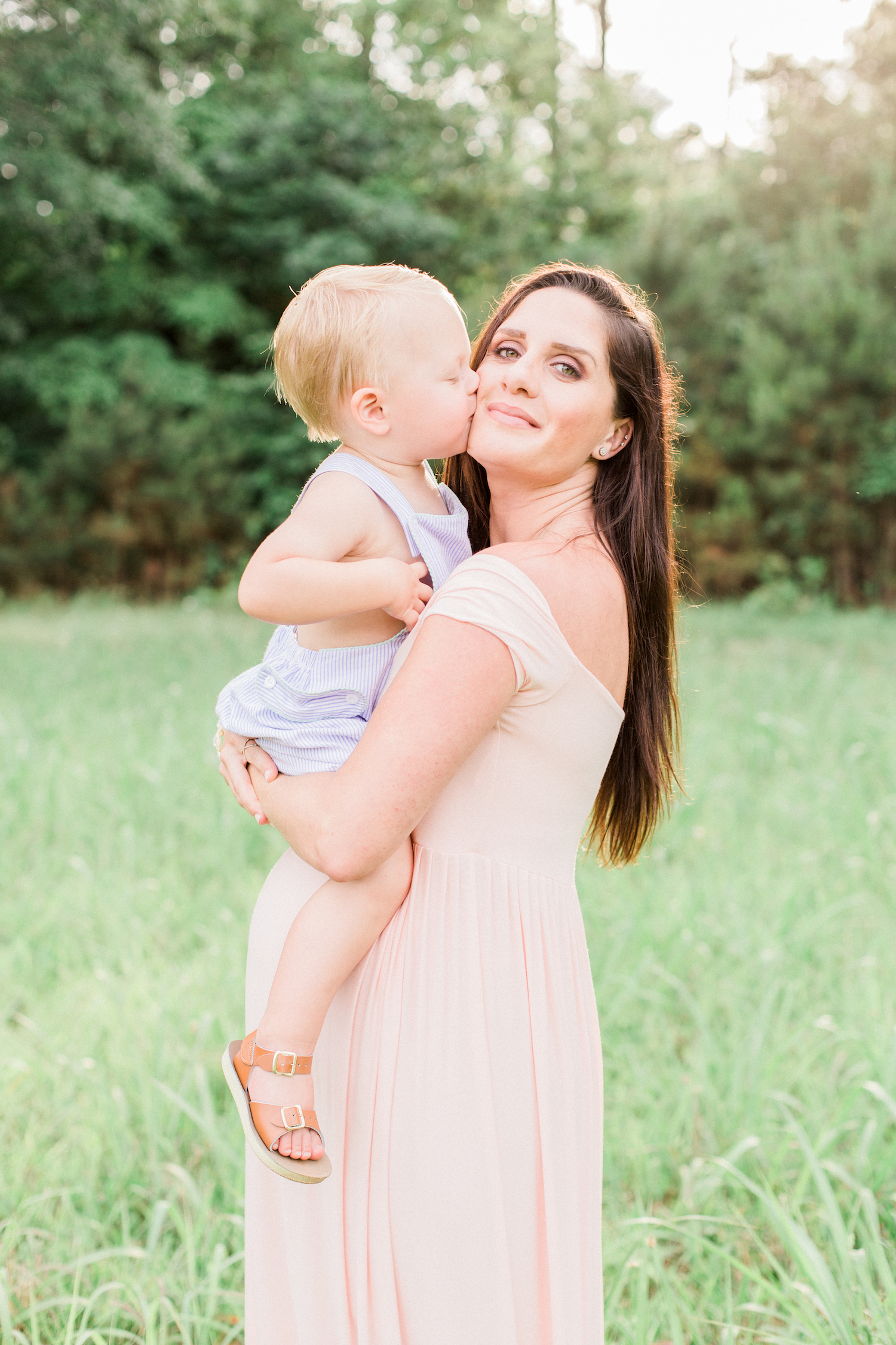 Mother and little boy during a spring time family session in Atlanta, Georgia. Wearing a blush pink maternity dress.