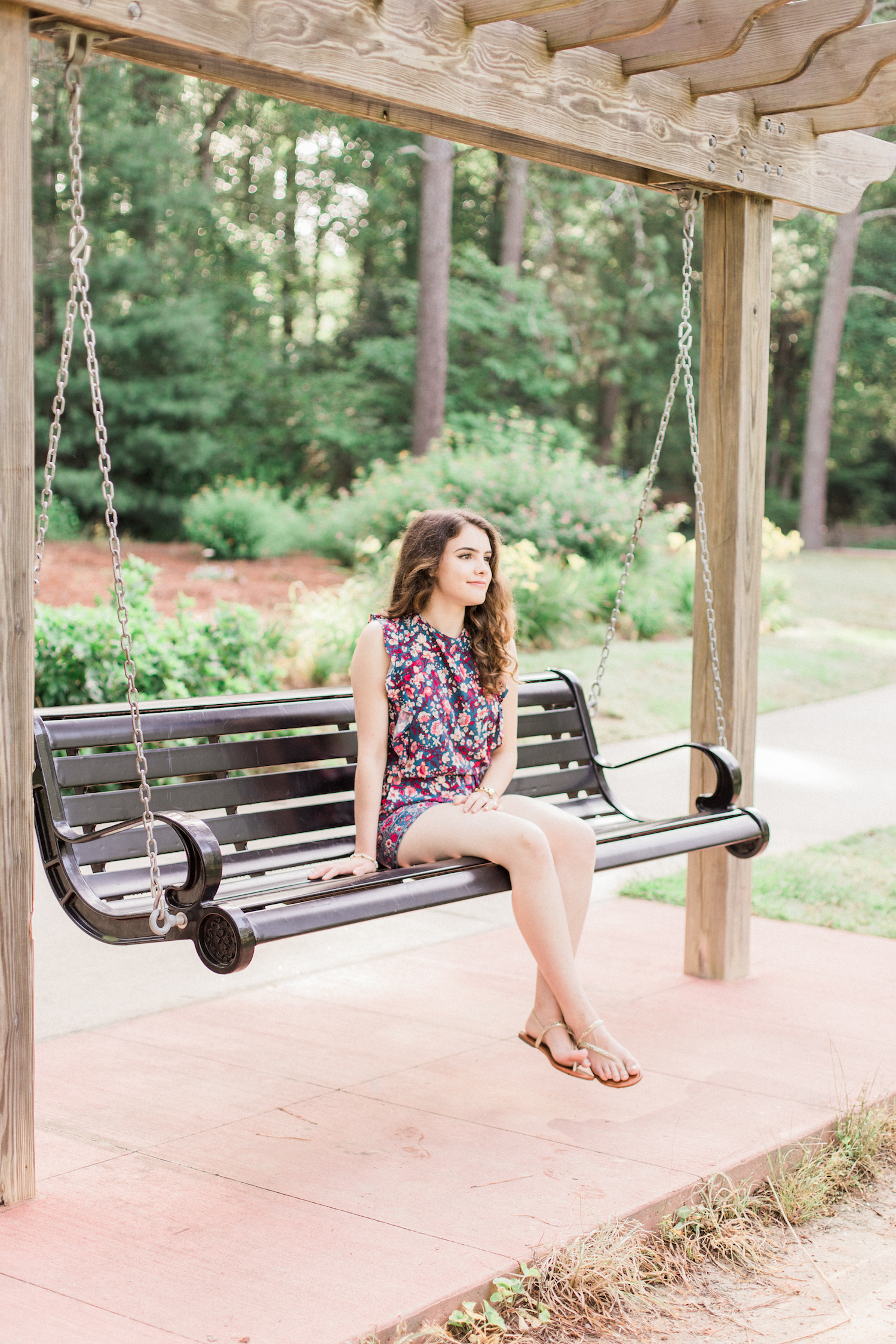 Summer time high school senior session at Vine Mansion Park by Kesia Marie Photography. Featuring feminine, garden details. Senior photos on a iron swing by a lake. Floral romper senior session style.