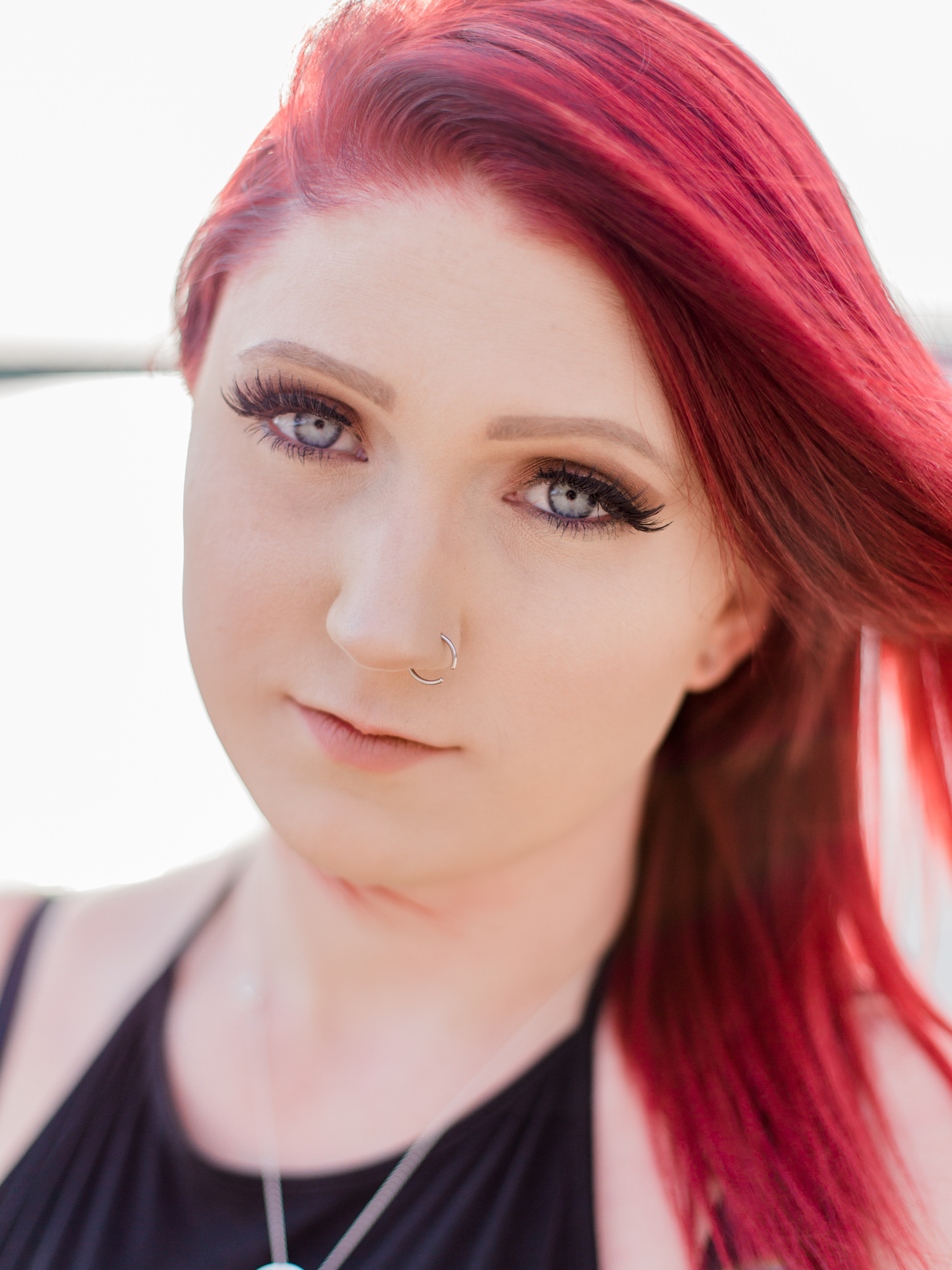 Edgy high school senior style- hoop nose ring, false eyelashes, and bright red layered hair. Senior session at a lake at Acworth Beach at Cauble Park in Acworth, Georgia. Photo by Kesia Marie Photography- fine art portrait photographer in Georgia.